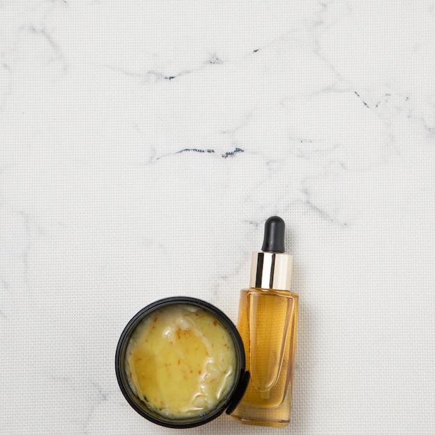 Disposizione piana della crema e della bottiglia di olio essenziale su fondo di marmo Foto Gratuite
