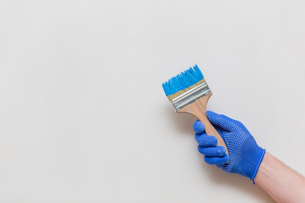 Disposizione piana della mano che tiene il pennello blu Foto Gratuite