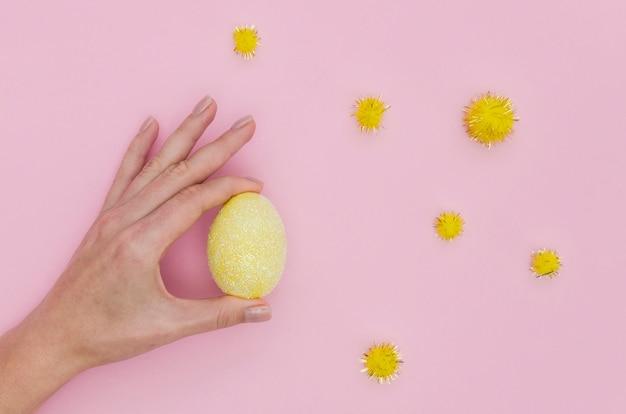 Disposizione piana della mano che tiene l'uovo di pasqua variopinto con i denti di leone Foto Gratuite