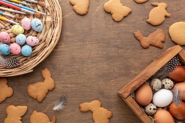 Disposizione piana della scatola con le uova per i biscotti a forma di coniglietto e di pasqua Foto Gratuite