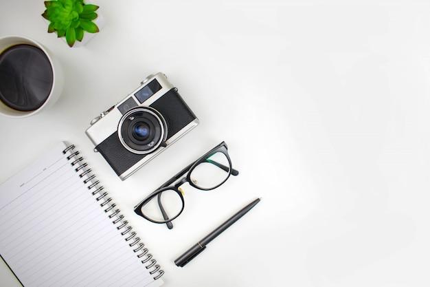 Disposizione piana della scrivania dell'area di lavoro degli accessori da viaggio con macchine da presa, occhiali, quaderni e caffè. con spazio di copia. Foto Premium