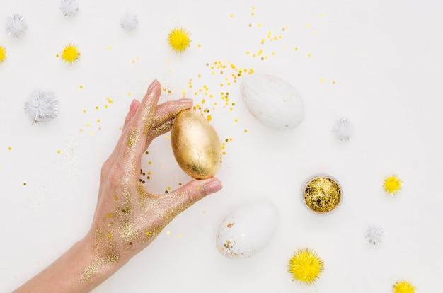 Disposizione piana della tenuta della mano che tiene uovo per pasqua con i denti di leone e lo scintillio Foto Gratuite