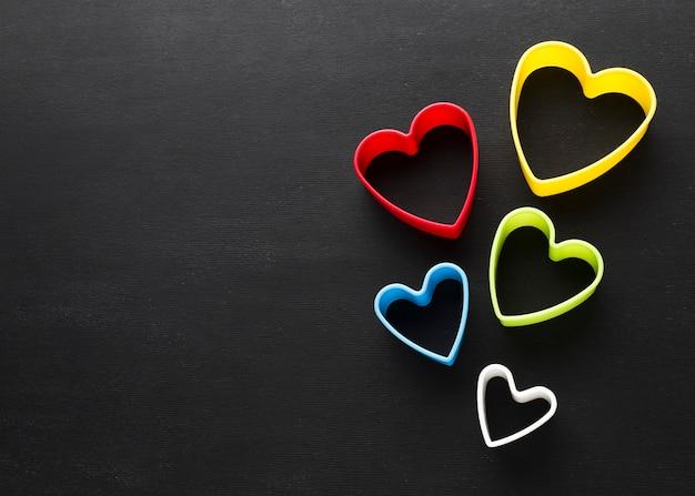 Disposizione piana delle forme colorate del cuore con lo spazio della copia Foto Gratuite