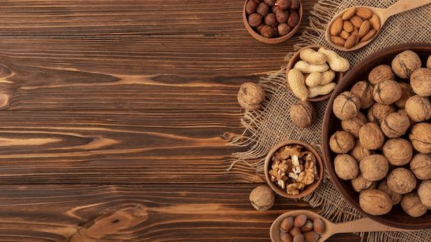Disposizione piana delle noci in ciotola con altra varietà di noci e spazio della copia Foto Gratuite