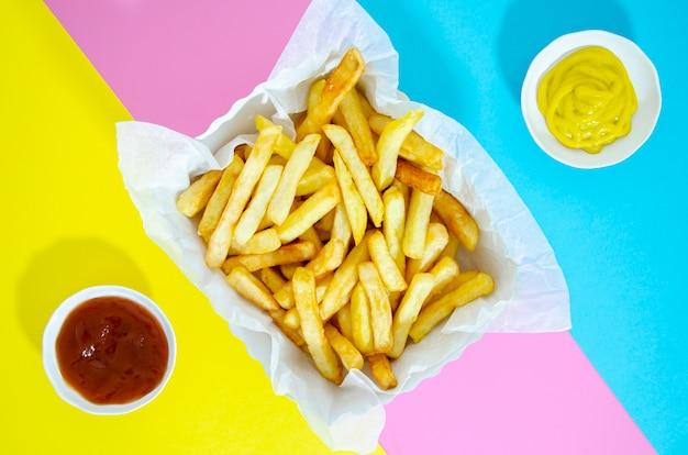 Disposizione piana delle patate fritte su fondo variopinto Foto Gratuite