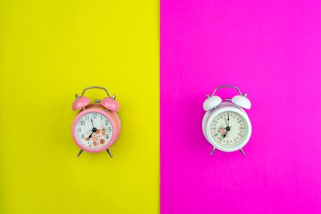 Disposizione piana di bella nuova sveglia sul fondo di carta pastello di carta rosa e giallo Foto Premium