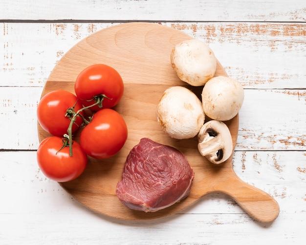 Disposizione piana di carne e verdure sulla tavola di legno Foto Gratuite