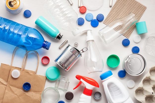 Disposizione piana di diversi rifiuti rifiuti pronti per il riciclaggio. plastica, vetro, carta, lattine Foto Premium