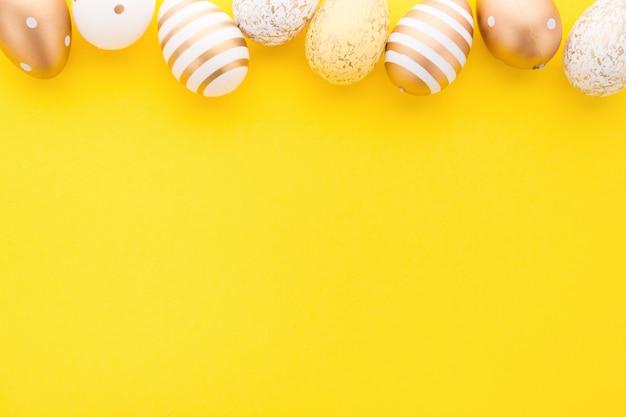 Disposizione piana di pasqua di uova su giallo Foto Gratuite