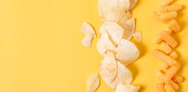 Disposizione piana di patatine fritte e sbuffi di formaggio con spazio di copia Foto Gratuite
