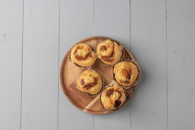 Disposizione piana di varietà di panetteria e maiale tagliuzzato danese sul bordo di legno Foto Premium