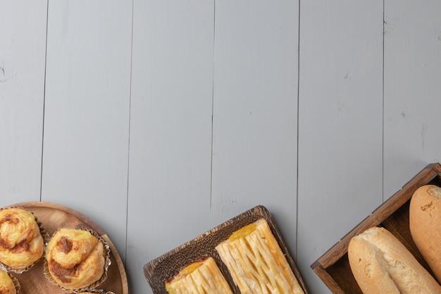 Disposizione piana di varietà di panetteria e pino di ananas su tavola di legno Foto Premium