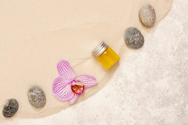 Disposizione piatta con olio, pietre e fiori Foto Gratuite