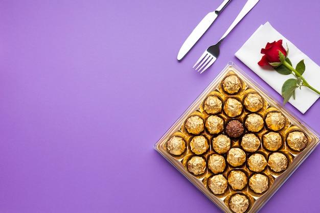 Disposizione piatta con scatola di cioccolatini e rosa Foto Gratuite