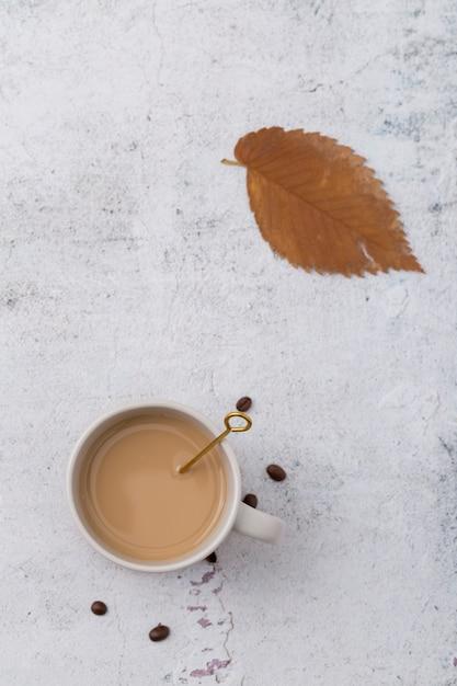 Disposizione piatta con tazza di caffè e foglia Foto Gratuite