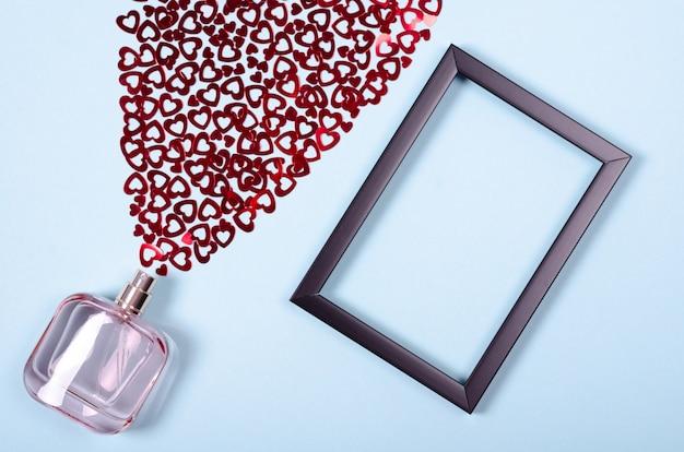 Disposizione piatta la disposizione dei cuori e bottiglia di profumo per mock up design Foto Premium