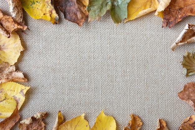 Disposizione piatta laica con foglie sulla trama sacco Foto Gratuite