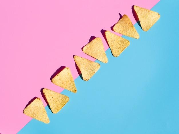Disposizione piatta laica con tortilla su sfondo rosa e blu Foto Gratuite