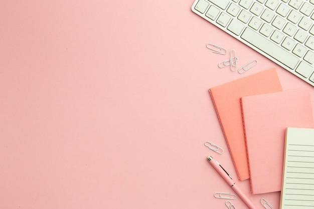 Disposizione piatta sul posto di lavoro rosa con spazio di copia Foto Gratuite