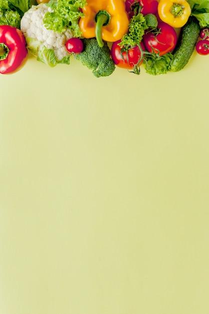 Disposizione sana e sana di cibo, alimento vegetariano e concetto di nutrizione di dieta. vari ingredienti degli ortaggi freschi per insalata sul fondo giallo della tavola, vista superiore, struttura, insegna. Foto Premium