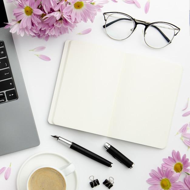Disposizione stazionaria di vista superiore sullo scrittorio con il taccuino vuoto Foto Gratuite