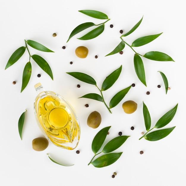 Disposizione sveglia di vista superiore di olio d'oliva e foglie Foto Gratuite