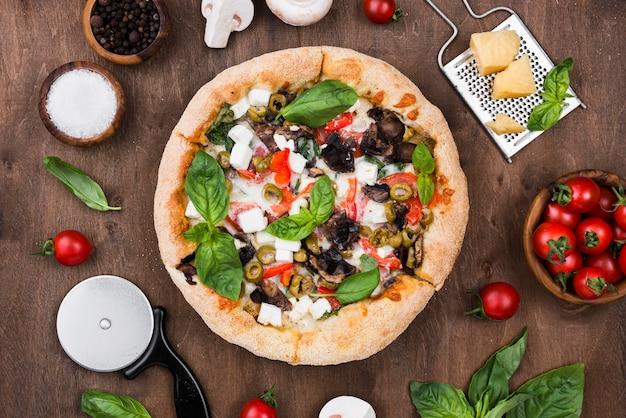 Disposizione vista dall'alto con pizza e spezie Foto Gratuite