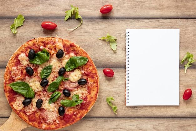 Disposizione vista dall'alto con pizza e taccuino Foto Gratuite