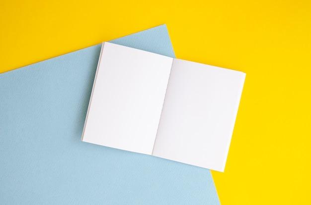 Disposizione vista dall'alto con taccuino bianco e sfondo colorato Foto Gratuite