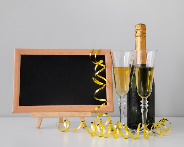 Disposizione vista frontale con lavagna mock-up e champagne Foto Gratuite
