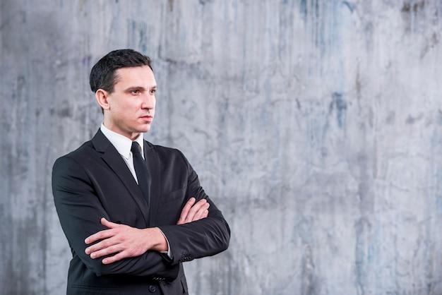 Distogliere lo sguardo dell'uomo d'affari con le braccia attraversate Foto Gratuite