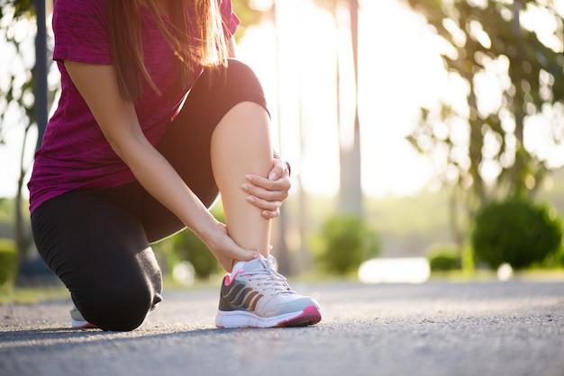 Distorsione alla caviglia. donna che soffre di un infortunio alla caviglia durante l'esercizio Foto Premium