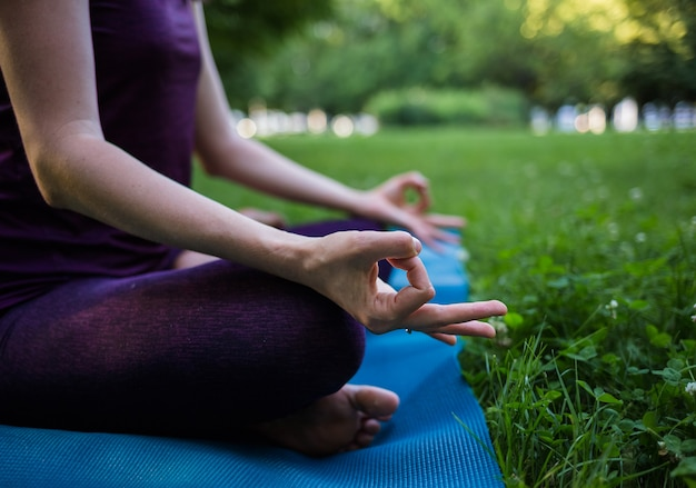 Dita di una ragazza che medita su una stuoia di yoga nel parco Foto Premium