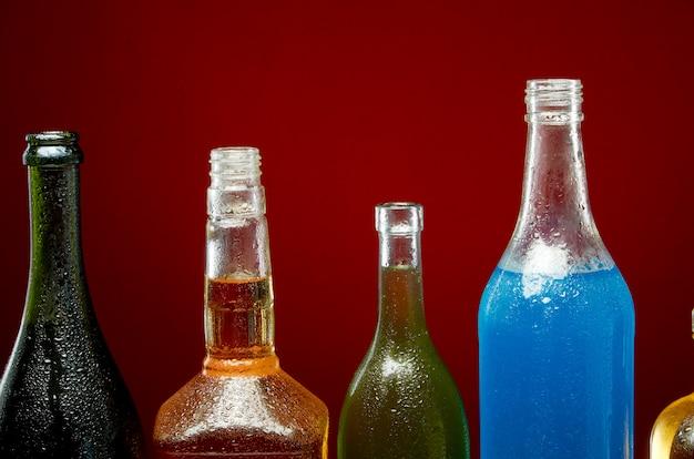 Diverse bevande alcoliche in bottiglie trasparenti su rosso Foto Premium