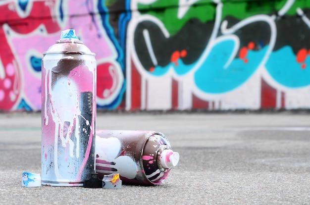 Diverse bombolette usate con vernice rosa e bianca e tappi per spruzzare vernice sotto pressione si trovano sull'asfalto vicino al muro dipinto in disegni colorati di graffiti Foto Premium