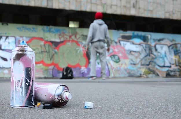 Diverse bombolette usate con vernice rosa e bianca giacciono sull'asfalto Foto Premium