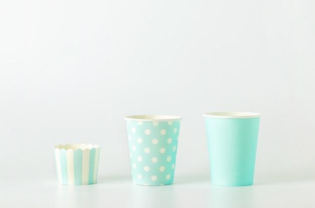 Diverse dimensioni della tazza di carta blu con pois bianchi e motivo a strisce su sfondo bianco Foto Premium