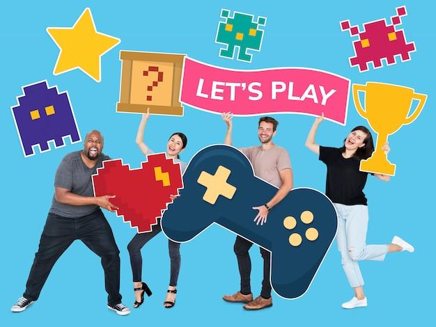Diverse persone giocose tenendo icone di gioco Foto Gratuite