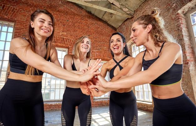 Diverse ragazze divertenti insieme in cerchio su stuoie di gomma che indossano il gesto sorridente di saluto di yoga di manifestazione degli abiti sportivi, esaminando macchina fotografica, cima sopra la vista. namaste, simbolo di saluto e apprezzamento Foto Premium