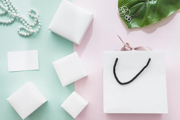 Diverse scatole bianche con shopping bag su sfondo rosa e verde Foto Gratuite