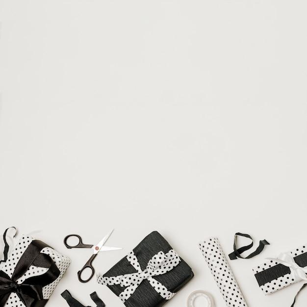 Diverse scatole regalo avvolte in bianco e nero con scissor e carta di design Foto Gratuite