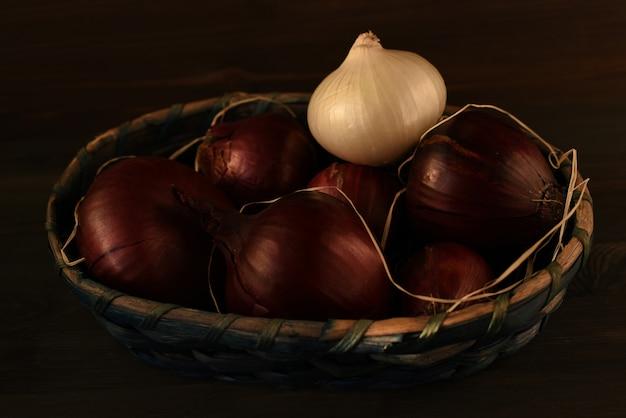 Diverse teste di cipolla rossa spagnola e una bianca piegate in un cesto di vimini Foto Premium