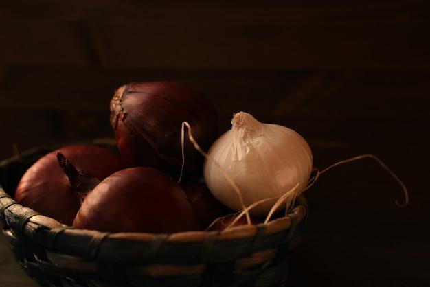 Diverse teste di cipolla rossa spagnola e una lampadina bianca sono piegate in un cesto di vimini. sfondo marrone scuro Foto Premium