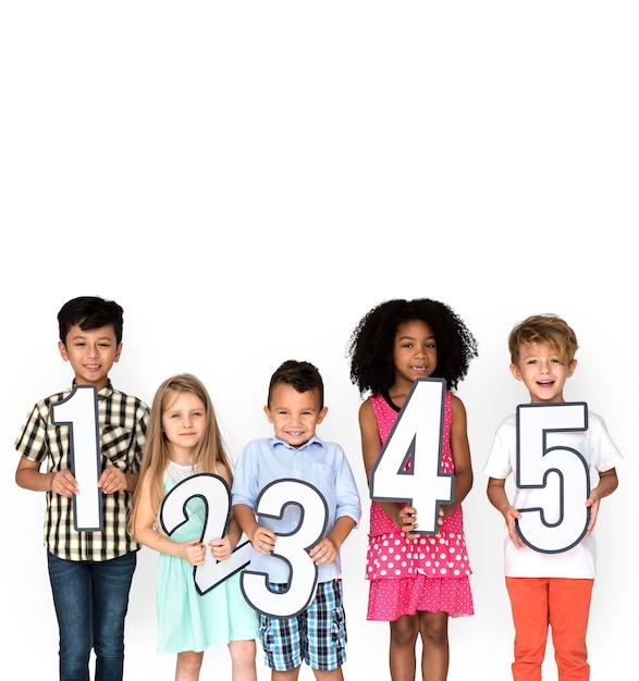 Diversi bambini che tengono i numeri 1 - 5 Foto Premium