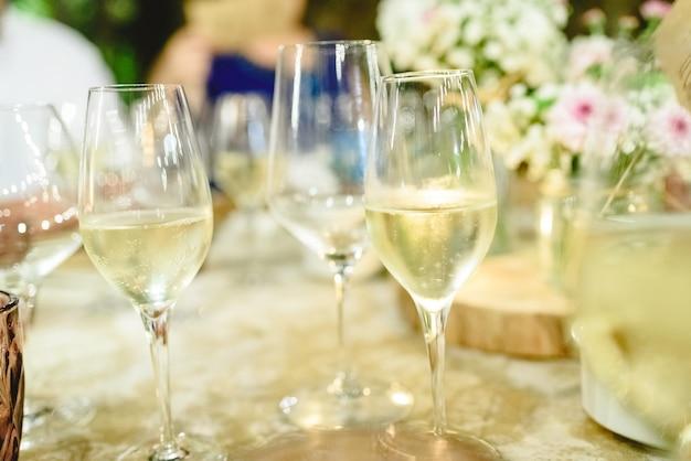 Diversi bicchieri di champagne frizzante e fresco servito sul tavolo di un banchetto. Foto Premium