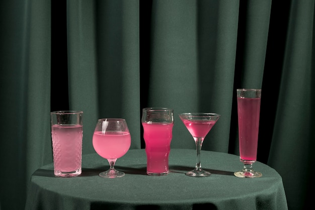 Diversi bicchieri pieni di liquido rosa sul tavolo Foto Gratuite