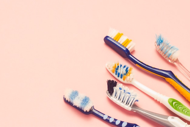Diversi diversi spazzolini da denti usati su uno sfondo rosa. concetto di cambio spazzolino, igiene orale, famiglia grande e amichevole, selezione spazzolino. vista piana, vista dall'alto. Foto Premium