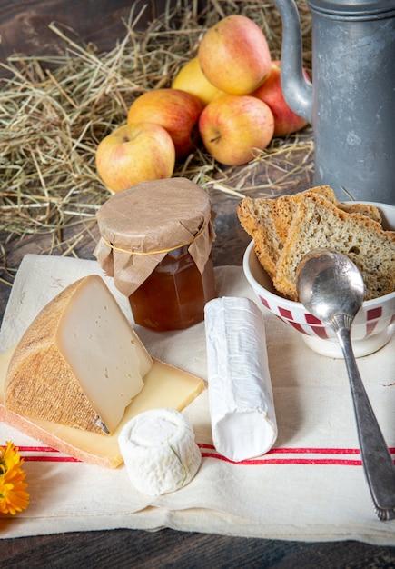 Diversi formaggi francesi con mele su paglia Foto Premium