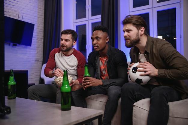 Diversi tifosi tifo per la squadra del cuore e bere birra a casa, copia spazio Foto Premium