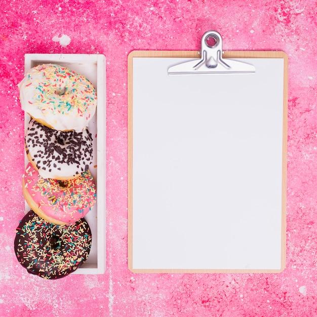 Diversi tipi di ciambelle in scatola rettangolare bianca vicino alla lavagna con carta bianca su sfondo rosa Foto Gratuite